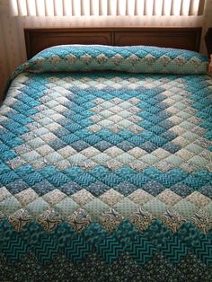 This modern Teal colored King Size hand-quilted quilt adds whimsyto your bedroom and is sure to delight! The fabrics used to create this fun quilt include zigzag prints, swirls, and geometrics. It was made with 100% cotton prints and measures approximately 108 by 114. It was pieced by sewing machine and then quilted by hand. The binding is double-folded, machine stitched on the front and hand-stitched on the back of the quilt. The batting is a high loft poly fill. New quilts that are quilted…