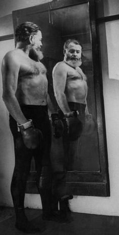 Author Ernest Hemingway admiring his mirror image bare-chested & sporting boxing gloves. He witnessed both world wars almost got killed in a plane crash and escaped death by horns of a bull. Indeed Ernest Hemingway was a mans man. (circa 1943)