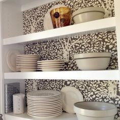Kitchen cabinets lined with wallpaper.
