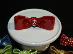 """2 1/2"""" red with deep red glitter. Bow has three rhinestones down the front. Polymer clay, handmade in the USA. One of a kind."""
