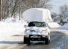 A vehicle, with a large chunk of snow on its top, drives along Route 20 after a massive snow fall in Lancaster, N.Y. Wednesday, Nov. 19, 2014. Another two to three feet of snow is expected in the area.