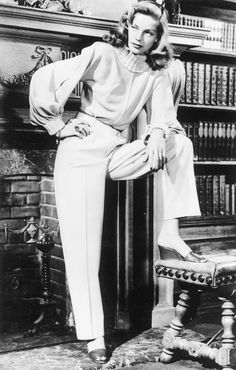 Lauren Bacall wears a high neck blouse with menswear-inspired trousers and sandals