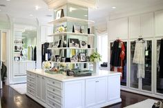 Luxurious, well-appointed, walk in closet features a stunning expansive island fitted with a mirrored pillar holding mounted white photo shelves and white shaker cabinets finished with polished nickel cup pulls.