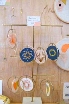 Embroidered decorations hanging off a simple brass stand at this craft fair display by Nook of the North at the Weekend of the Maker in Sheffield