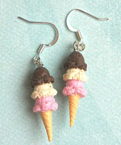 these adorable earrings feature a pair of neapolitan ice cream charms. these sweet treats are handmade from polymer clay and measures an inch in length. both minis hang from a silver tone hook. the en