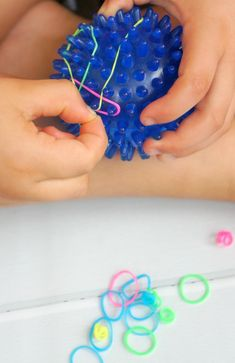 Fine motor activity for kids, toddlers and preschoolers using a soft spiky ball and loom bands. #finemotorskills #loombands #ot