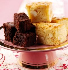 A pile of brown and white brownies on a pink cake stand