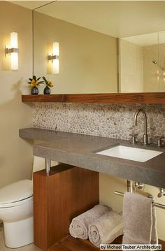 The cement counter with the pebble wall splash and wooden shelf is beautiful!