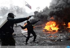 UKRAINE, Kiev : A protestor points a gun during clashes with riot police in the centre of Kiev on January 22, 2014. Ukrainian police today stormed protesters' barricades in Kiev as violent clashes erupted and activists said that one person had been shot dead by the security forces. Total of two activists shot dead during clashing. EU. AFP PHOTO/ VASILY MAXIMOV