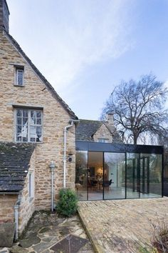 A modern glass kitchen extension built onto this listed cottage in the countryside has created a luxurious open plan living space, adding a modern touch to the old brick cottage. Cottage Extension, House Extension Design, Glass Extension, House Extension Plans, Garden Room Extensions, House Extensions, Cotswold House, Glass House Design, Brick Cottage