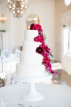 A super simple white wedding cake with a gorgeous cascade of red and pink flowers   Photograph by Sarah Bradshaw Photography