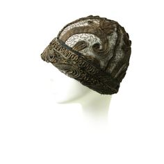 Beautiful cloche dates to the 1920's and is made of gold bullion sewn onto metallic lace. Bullion is arranged in a scrolling floral pattern. Unlined. Crown is constructed of four pie shaped pieces.
