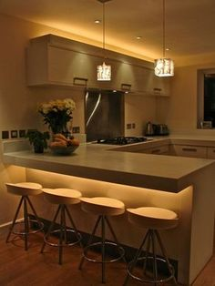 Contemporary kitchen with under-counter and above-cabinet lighting.