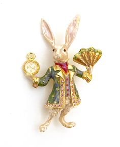 Retired Kirks Folly White Rabbit Brooch  This beautiful highly collectible brooch is crafted in gilt metal  - Covered in multi-colored enameling - Accented with pink rhinestones  - The rabbits jacket is so wonderful in a stunning shade of green  with Ace of Spades, Clubs, Hearts, and Diamond patterns and has  a border of pink rhinestones  - In one hand the rabbit is holding a beautiful gilt fan that is edged in green crystals - His other fan is holding a enameled clock  Measures: Approx. 3 x…