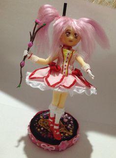 Olá, vim mostrar a primeira boneca de meu projeto de criar Figuarts a mão! <br>A primeira boneca é Madoka Kaname, ela é feita de porcelana fria, a roupa de tecido e o cabelo é de lã turca. <br> <br>Ela tem uma base que a deixa ficar de pé. Ela é cheia de detalhes, demorei 1 mês para terminá-la. <br>Essa é uma boneca OOAK (One of a Kind - única a ser feita). <br> <br>Ao comprar essa boneca saiba que estará comprando uma peça única. <br> <br>O valor dessa figura da Madoka Magika é de: R$50…