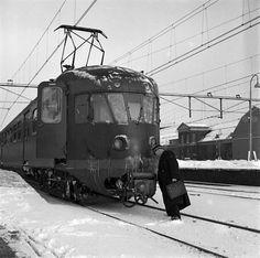 1956 een wagenvoerder (machinist) bij de automatische koppeling van een electrisch treinstel mat. 1946 (plan B) van de N.S. bij het N.S.-station Utrecht C.S. te Utrecht, in de sneeuw.