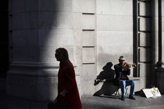 A man plays a trumpet for money at Madrid's main Gran Via avenue in Madrid, Spain on Oct. 31. Gran Via is a lively shopping street mixed with theatres, cinemas and music halls in the heart of the city. (Francisco Seco/Associated Press)