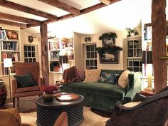 Cozy family room in restored 18th century home with built-in bookcases, dog art, green velvet sofa - Lisa Hilderbrand