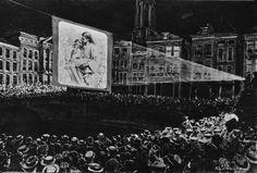 """1911 - Openluchtsamenkomsten Het lukt het Leger des Heils om met moderne middelen mensen met het Evangelie te bereiken. In Utrecht bijvoorbeeld vertoont de organisatie lichtbeelden op de Oude Gracht, waarbij naar schatting zo'n tienduizend mensen aanwezig zijn. Zij kijken met grote belangstelling naar de uitnemende beelden op het doek. """"'t Was in één woord een indrukwekkende evangelische vertooning!"""", aldus een bekend Nederlands weekblad in dat jaar."""