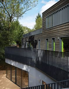This new building added to a school in Beaconsfield by London architecture office DSDHA flanks a tree-lined playground and is clad in waney-edged timber.