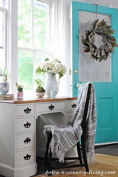 farmhouse entry, antique desk & teal door with a magnolia wreath