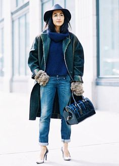 A ribbed turtleneck is paired with a green coat, cuffed jeans, furry mittens, pumps, a fedora, and a satchel