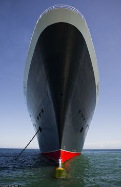 Captain Kevin Oprey stands on the bulbous bow of the Queen Mary 2 off the coast of Bali in photographs taken to mark the ocean liner's tenth...