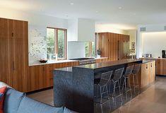 Bertoia barstools are tucked under a custom honed-granite kitchen island.