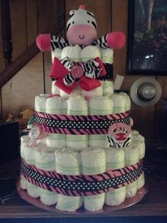 """The Cake I created for the shower I was throwing. The inside has 2 10oz baby bottles filled with Dove chocolate, and there are also 5 rolled onesies along with the diapers. There are 5 pacifiers attatched and a teething key toy for the baby on the back. The """"J"""" bow hairband attached is from Gabella's Bowtique in Plymouth PA!"""