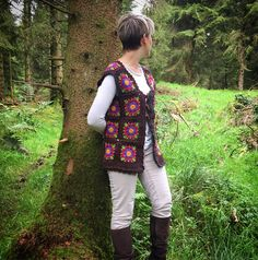 Brand new and hand crafted - this unique waistcoat is made from individual granny squares. Each has a flower motif at the centre with a mustard middle, purple and dark pink petals and moss green leaves. The squares are all edged with a marbled brown yarn. This yarn is used for a