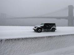 Carro passa por rua coberta por neve em frente à ponte do Brooklyn neste sábado (23) durante nevasca em Nova York (Foto: REUTERS/Carlo Allegri)