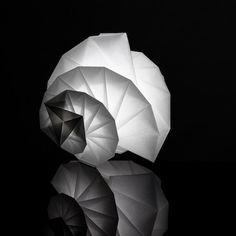 Dévoilée durant les Designer's Days, IN-EI est une collection de luminaires développée par Issey Miyake pour Artemide. Leur forme est issue du projet de recherche « 132 5. ISSEY MIYAKE », qui explore les principes de géométrie tridimensionnelle du mathématicien Jun Mitani.    Les lampes, réalisées en PET recyclé et alimentées par des Leds, proposent ainsi des volumes tridimensionnels complexes, capables de se stocker à plat lorsqu'ils sont repliés.