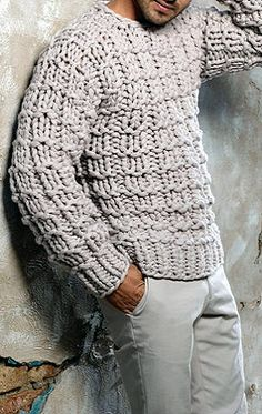 Men's soft gray cotton hand-knit sweater over slacks of the same shade.