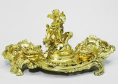 Inkstand Unknown maker About 1880 Gilt brass, with brass and glass liners at the VA museum, London Rococo revival style of the late 19th century: in Britain it was called the French Style and rococo was one of its key elements. Elaborate forms and the use of S- and C-shaped scrollscharacterizeboth styles.Objects were highly ornate.