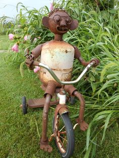 Junk repurposed into garden art boy on tricycle -