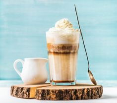 #Latte macchiato with whipped cream  Latte macchiato with whipped cream serving silver spoon and pitcher on wooden round board over blue painted wall background selective focus horizontal composition