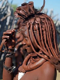 Namibia, Kaokoland. A Himba woman in traditional attire adjusts her headdress. Her body gleams from a mixture of red ochre, butterfat and herbs. Her long hair is styled in the traditional Himba way and is crowned with a headdress made of lambskin, called e