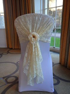 Lace chair hood with flower, ideal for a romantic, vintage style wedding. From Lovely Weddings.