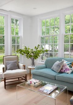 Sun filled living space is filled with a blue roll-arm sofa facing a CB2 Peekaboo Acrylic Coffee Table, A wood chair upholstered in beige linen fabric is placed next to a round marble and brass end table topped with flowers.