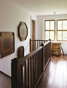 A dark wood Mission-style banister contrasts with the white walls and ceilings. Keeping the floor planks and beadboard ceiling running in the same direction helps draw the eye to the back, where antiq