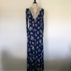 """Vtg 70s S M Blue Floral Crochet Corset Maxi Dress Long sleeve floral maxi dress features corset front and beige crochet chest and sleeve detail. Empire waist with back ties and Aline bottom. Zips and hooks in back. Flaws: Tear (repaired by me) on right shoulder, yellowing on crochet at neck, """"purple"""" spots in blue fabric, and sleeves look to be hemmed. Price reflected.  Brand: N/A Material: N/A (Feels like Polyester) Size: 9 (Fits like a S/M) Bust [Laced]: 32-37 Waist: 26-28 Hips: 38-42…"""