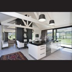 The light and airy interior is enhanced by blonded wood floors, white-painted sarking and exposed roof trusses.
