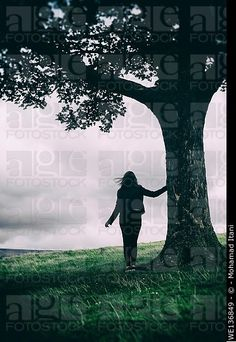 Silhouette of a female figure leaning against a tree in the countryside. © Mohamad Itani / age fotostock - Stock Photos, Videos and Vectors