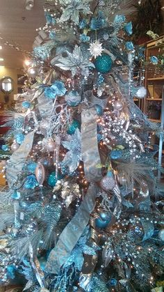 The Tiffany Tree That special blue box you never forget was the inspiration for this elegant Tiffany blue tree with champagne ribbon laced through the boughs of the blue spruce host tree. Ornaments embellished with platinum on a Tiffany blue background are scattered about and this tree glistens as if touched by an ice storm. Find more Christmas tree inspiration at Persimmon Lane!