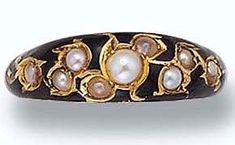 Princess Margaret's  18-carat gold ring bezel-set with seed pearls, surrounded by a rim of metal, and the gaps coated with black enamel. There are nine seed pearls mounted on the ring - made in the year 1891.