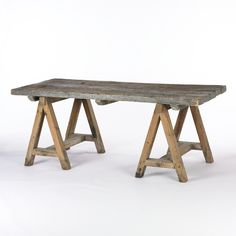 Rustic wood dining table with sawhorse legs. Wood varies in color and texture. W: 76.5 in × D: 34 in × H: 30.5 in