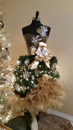 My take on a mannequin christmas tree. I used chicken wire for the base of the skirt and attached bunches of artificial garland. I made the bow from 2 types of ribbons and then accessorized with gold and white snowflakes.