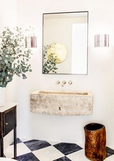 Modern bathroom with a floating stone sink carved from a boulder and a wood stool