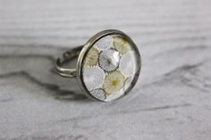 Cette jolie bague représente un motif fleurit japonisant gris et ocre sur lequel est fixé un cabochon loupe en verre. Elle s'adapte à tous les doigts. Elle apportera de l'élégance à votre main.  Diamètre du cabochon en verre : 20 millimètres