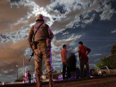Ciudad Juárez, México, 22 de septiembre de 2013 - Un soldado junto a un guardia cerca de una escena de crimen en Loma Blanca, en las afueras de Ciudad Juárez. Desde diciembre de 2006, el gobierno mexicano ha estado peleando una guerra con los carteles de drogas, que también pelean mutuamente por el territorio. La violencia ha matado a más de 60.000 personas.